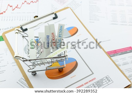 Various type of financial and investment products in a shopping cart i.e. REITs, ETFs, bonds, stocks. Sustainable portfolio management, long term wealth management with risk diversification concept. - stock photo