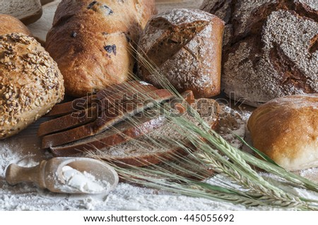 Various types of bread and cereal ears on a wooden table with flour.