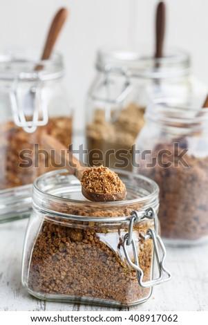 Various types of brown sugar in glass jars - stock photo