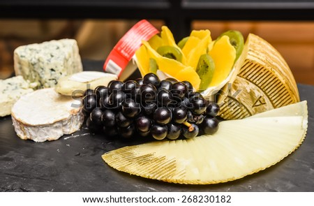 Various types of cheese and fruits - stock photo