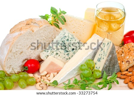 Various types of cheese and garnishes on wooden plate