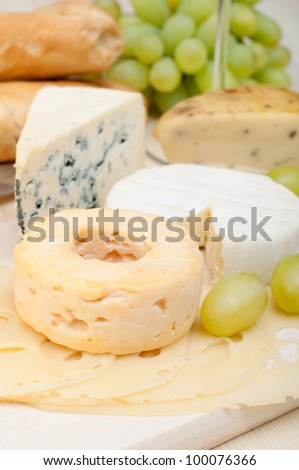 Various Types of Cheese and Grapes on Wooden Chopping Board - stock photo
