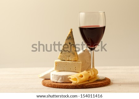 Various types of cheese and red wine - stock photo