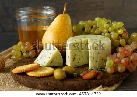 Various types of cheese, fruits and appetizers