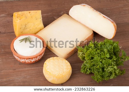 Various types of cheese on a wooden background with parsley