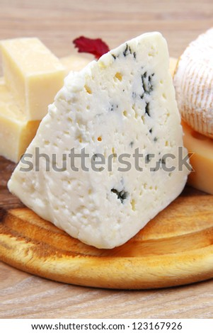 various types of cheese on wooden platter over wooden table - stock photo