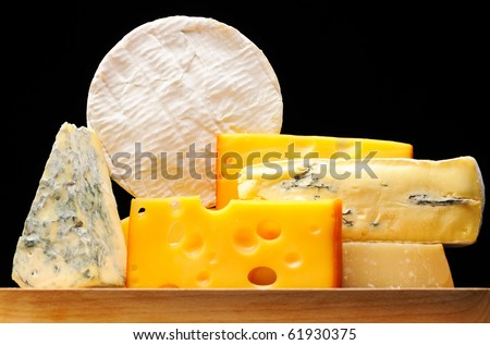 Various types of cheese over black - swiss, parmesan, mold, camembert - stock photo