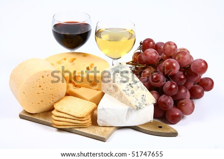Various types of cheese (swiss, yellow, brie, blue cheese) with red and white wine, red grapes and crackers on white background