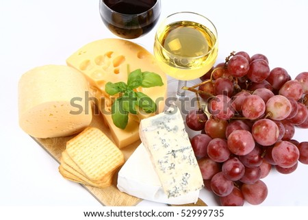 Various types of cheese (swiss, yellow, brie, blue cheese) with red and white wine, red grapes and crackers in close up on white background