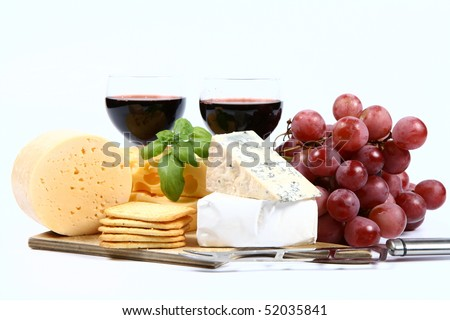 Various types of cheese (swiss, yellow, brie, blue cheese) with red wine, red grapes and crackers and cheese knife on white background