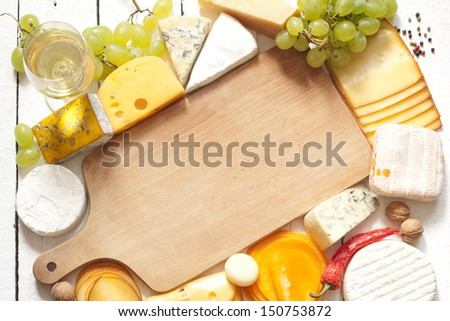 Various types of cheese with empty cutting board background concept - stock photo