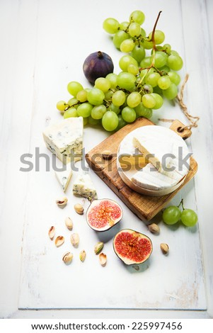 various types of cheese with figs and grapes - stock photo