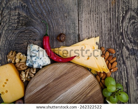 Various types of cheese with nuts and grapes on wooden background - stock photo