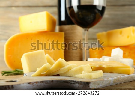 Various types of cheese with wine on table close up - stock photo