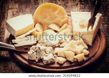 Various types of cheese,wooden old table,vintage filter - stock photo