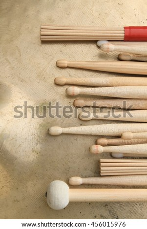 Various types of drum sticks in a row and placed on a cymbal - stock photo