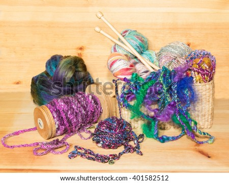 Various types of fancy art yarns in a basket with a spindle and a wool fleece, ready to knit.