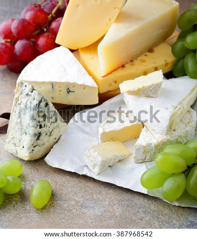 Various types of fresh Cheese with grapes on slate. Closeup - stock photo