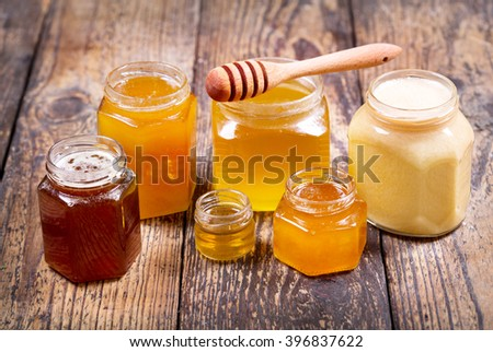 various types of honey in glass jars on a wooden table - stock photo