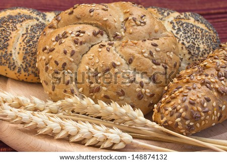 Various types of whole wheat bread and wheat ears lying on a wooden board.