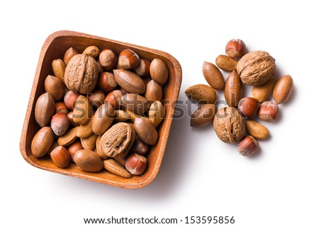 various unpeeled nuts in wooden bowl on white background - stock photo