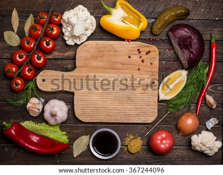 Various vegetables and spices and empty old cutting board. Colorful ingredients for cooking on rustic wooden table around empty cutting board with copyspace. Top view. Retro styled. - stock photo
