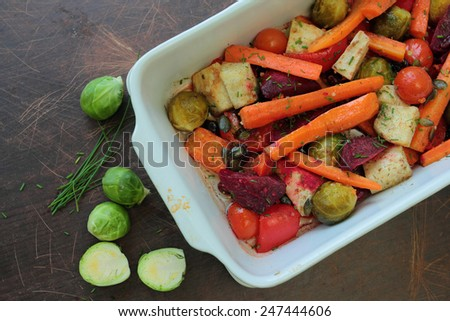 Various vegetables roasted in oven-pan with carrots, beetroots, tomatoes and brussels sprouts - stock photo