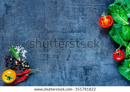 Various vegetarian ingredients (spinach, tomatoes, spices and herbs) on dark vintage table, top view. Healthy food, vegan or diet nutrition concept. Background layout with free text space. - stock photo