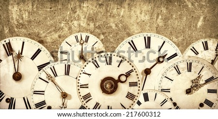 Various vintage clock faces in front of an old concrete wall - stock photo