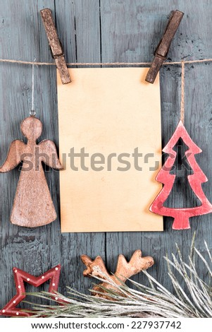 Various vintage decorations in the shape of Christmas tree and  angel and blank greetings card hanging on string on old wooden background vertical - stock photo