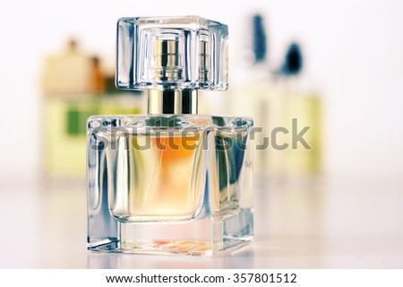 Various woman perfumes set on light background. Selective focus on front bottle, shallow DOF. Filtered toned image. - stock photo