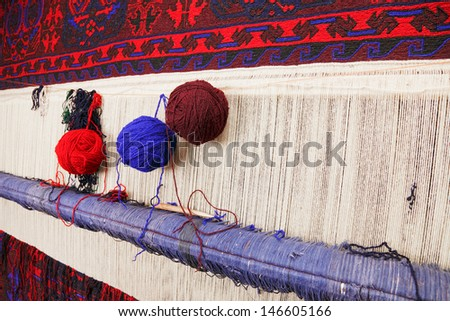 Various yarn on weaving handmade carpet - stock photo