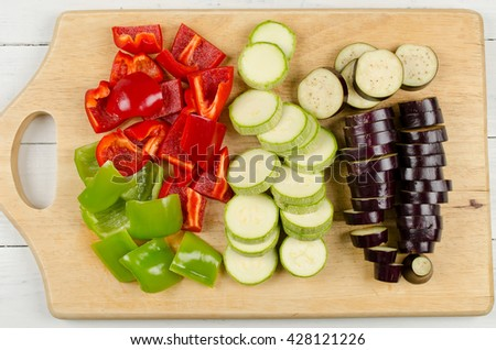 Variously sliced for cooking zucchini, eggplant and paprika on a cutting board. Preparation of vegetables on a wooden table - stock photo