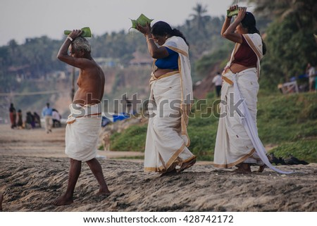 VARKALA, INDIA - DEC 15, 2012:  Pilgrims walk down to the sea to offer puja. This is a holy place. Pilgrims come here to take a holy dip in the holy waters of the beach. - stock photo