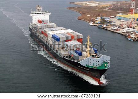 VARNA, BULGARIA - DECEMBER 14: Cargo ship WARNOW VAQUITA (Year Built: 2008) sails into open sea on December 14, 2010 in Varna, Bulgaria. Ship`s next destination is Constanta, Romania. - stock photo