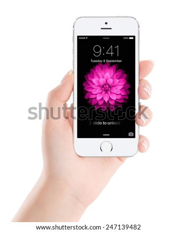Varna, Bulgaria - December 07, 2013: Female hand holding Apple Silver iPhone 5S with lock screen on the display, designed by Apple Inc. Isolated on white background. - stock photo