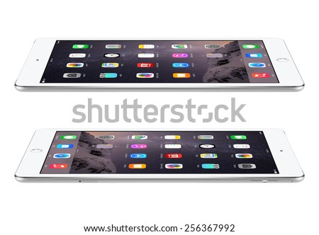 Varna, Bulgaria - February 04, 2014: Apple Silver iPad Air 2 with touch ID displaying iOS 8 homescreen lies on the surface, left and right side view, designed by Apple. The whole image in focus. - stock photo