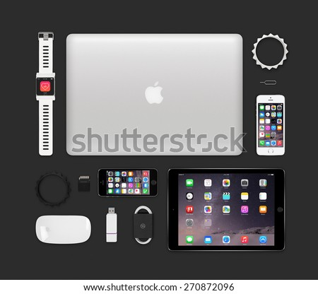 Varna, Bulgaria - February 11, 2015: Top view of Apple products tech mockup that includes retina macbook pro, ipad air 2, smart watch concept, iphone 5s, magic mouse, flash drive, bracelets.  - stock photo