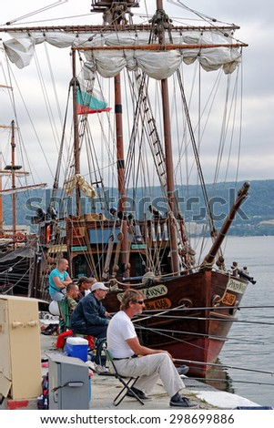 Varna, BULGARIA - June 21, 2015: Group of men are fishing next to a pirate ship replica in Port of Varna. Such wooden vessels are mainly used as attraction for tourists during the summer season.  - stock photo