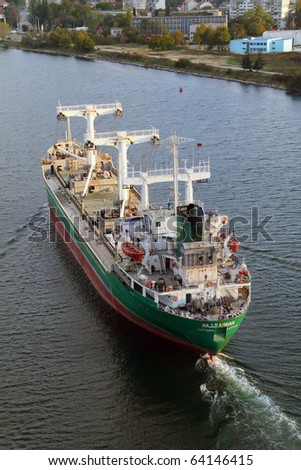 VARNA, BULGARIA - OCTOBER 31: Cargo ship HAJJI AMNAH (Flag: Syria) sails away into open sea after delivering 7700 t of phosphorite to Varna-West Port on October 31, 2010 in Varna, Bulgaria. - stock photo