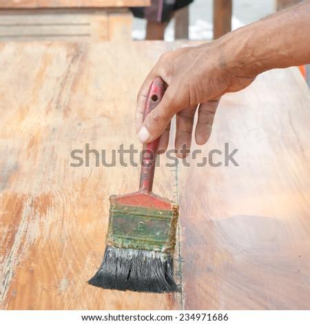 Varnishing antique wooden table  using paintbrush - stock photo