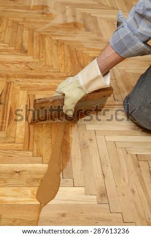 Varnishing of oak parquet floor, senior workers hand and tool - stock photo