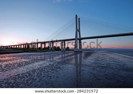 Vasco da Gama Bridge at sunset in Lisbon Portugal - stock photo