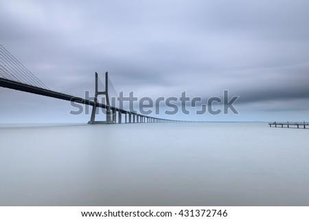 Vasco da Gama Bridge is an amazing landmark in Lisbon. One of the biggest bridges in the world, is an amazing spot for many landscape photographers. Long exposure effect. - stock photo
