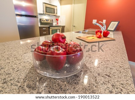 Vase filled with some apple fruits on the counter, table with the kitchen on the back. Interior design. - stock photo