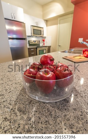 Vase filled with some fruits, apples and pomegranates on the counter, table with the kitchen on the back. Interior design. - stock photo