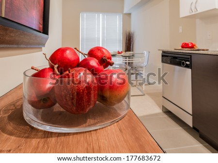 Vase filled with some pomegranates, apples fruits on the kitchen table with dining table on the back. Interior design. - stock photo