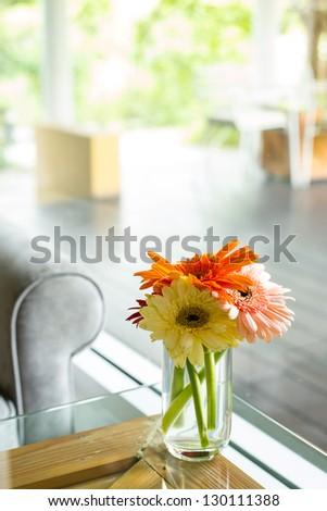 Vase full of  colorful flowers on glass table with sofa at Cafe