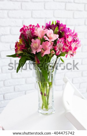 Vase full of colorful flowers on table