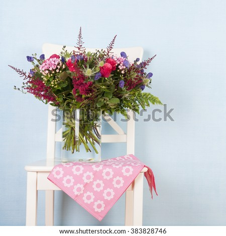 Vase mixed bouquet flowers on chair with blue background - stock photo